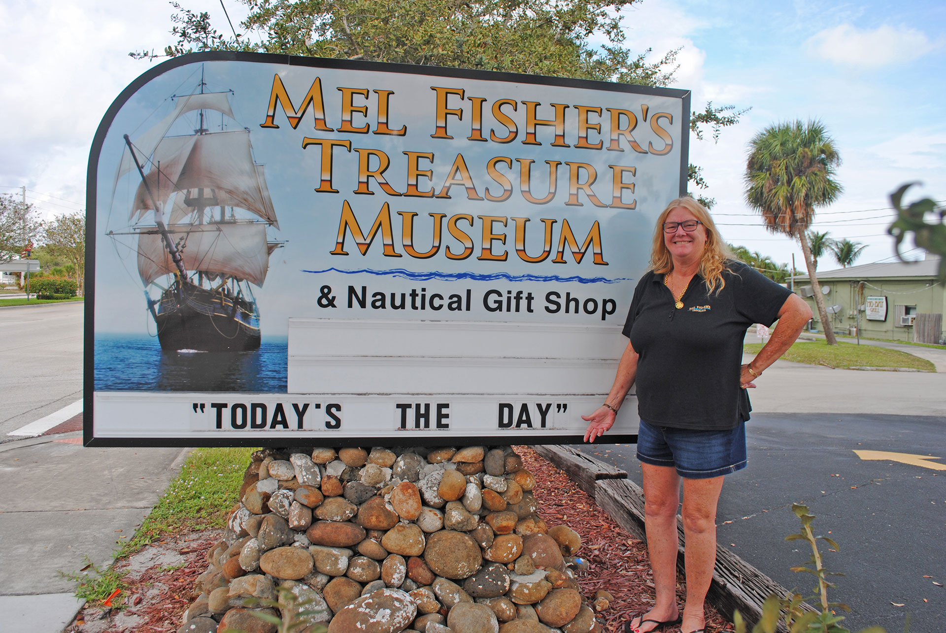 Taffi Fisher Abt, a partner in the family salvage business, had her father's motto added to the sign outside of Mel Fisher's Treasure Museum and Gift Shop. KERRY FIRTH PHOTO